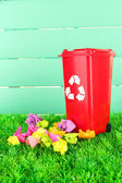 Recycling bin with papers on grass on light blue background — Stock Photo