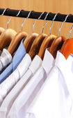 Men's shirts on hangers in wardrobe — Stock Photo