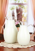 Pitchers of milk on table in room — Stock Photo
