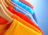 Lots of T-shirts on hangers on blue background — Foto Stock