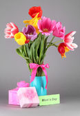 Beautiful tulips in bouquet with gifts and note on gray background — Stock Photo