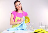 Beautiful young woman wipes clean utensils in kitchen on grey background — Stock Photo