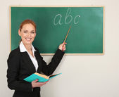 Portrait of teacher woman near chalkboard in classroom — Stock Photo