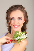 Mujer joven con peinado hermoso y flores, sobre fondo gris — Foto de Stock