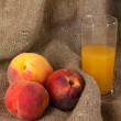 Ripe peaches and juice on sacking — Stock Photo