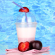 Delicious milk shake with fruit on table on blue sea background — Stock Photo