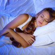 Young beautiful woman with toy bear sleeping on bed in bedroom — 图库照片