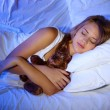 Young beautiful woman with toy bear sleeping on bed in bedroom — Stock fotografie