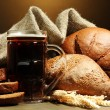 Tankard of kvass and rye breads with ears, on wooden table on brown background — Stock Photo #23521403