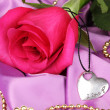 Beautiful pink rose with heart pendant — Stock Photo #23521561