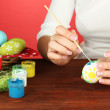 Stock Photo: Young woman painting Easter eggs, on color background