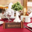 Reserved sign on restaurant table with empty dishes and glasses — Stock Photo #23522539