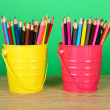 Colorful pencils in two pails on table on green background — Stock Photo #23522623