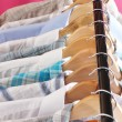 Men&#039;s shirts on hangers on pink background - Stock Photo