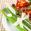 Festive dining table setting with flowers on checkered background — Stock Photo #23523101