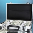 Suitcase with 100 dollar bills on blue background — Stock Photo #23523693