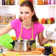 Young woman cooking in kitchen — Stock Photo #23523857