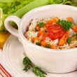 Delicious rice with vegetables and herbs in pot on wooden table close-up — Stock Photo