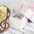 Treble clef, flower and box holding wedding ring on musical background — Stock Photo