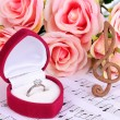 Treble clef, roses and box holding wedding ring on musical background — Stock Photo #23524139