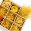 Nine types of pasta in wooden box sections isolated on white — Stock Photo