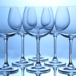 Empty wine glasses arranged on blue background — Stock Photo #23525607