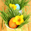 Easter eggs in bowls with grass on wooden table close up - Stock Photo