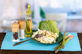 Plate with coleslaw and seasonings on wooden table on room background — Stock Photo