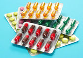 Capsules and pills packed in blisters, on blue background — Stock Photo