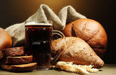 Tankard of kvass and rye breads with ears, on wooden table on brown background — Stock Photo