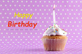 Tasty birthday cupcake with candle, on purple background — Stock Photo