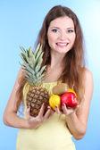 パイナップルと青色の背景に果物と美しい女性 — ストック写真