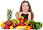 Beautiful woman with vegetables and fruits on table isolated on white — Stock Photo
