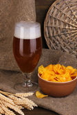 Glass of beer with plate of chips on wooden table on sacking background — Stock Photo