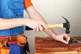 строитель, забивая гвозди в совет на сером фоне — Стоковое фото