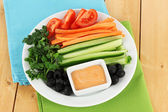 Assorted raw vegetables sticks in plate on wooden table close up — Stock Photo
