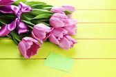 Vacker bukett lila tulpaner på grön trä bakgrund — Stockfoto
