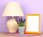 Barevné foto rámeček, lampu a květiny na dřevěný stůl na lila pozadí — Stock fotografie