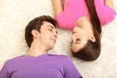 молодая пара, лежа на спине на дому — Стоковое фото