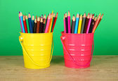 Colorful pencils in two pails on table on green background — Stock Photo