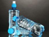 灰色の背景上の別の水のボトル — ストック写真