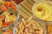 Different types of pasta on striped tablecloth — Stock Photo