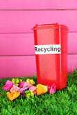 Recycling bin with papers on grass on pink background — Stock Photo