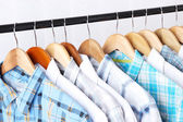 Men's shirts on hangers on light background — Stock Photo