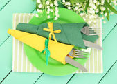 Forks and knives wrapped in green and yellow paper napkins, on color wooden background — Stock Photo