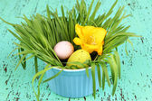 Easter eggs in bowl with grass on green wooden table close up — Stock Photo