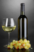 White wine glass and bottle of wine on grey background — Stock Photo