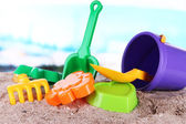 Children's toys on sand on sea background — Stock Photo