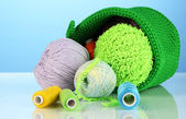 Colorful yarn for knitting in green basket on blue background — Stock fotografie
