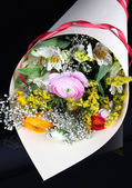 Bouquet of various flowers on dark background — Stock Photo
